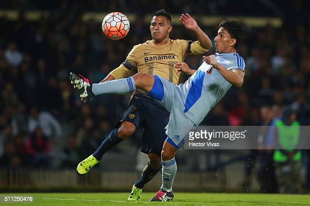 Angel Mena of Emelec struggles for the ball with Javier Cortes of Pumas during the group 7 match between Pumas UNAM and Emelec as part of Copa...