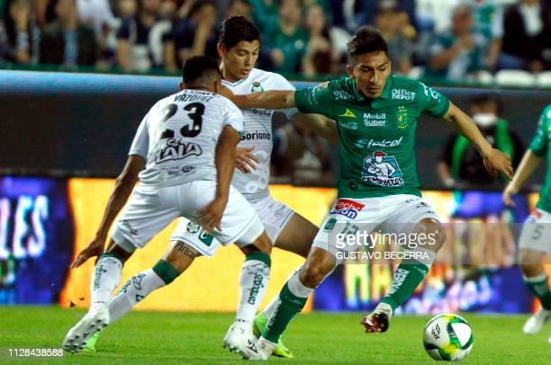Angel Mena of Leon vies for the ball with Jose Vazquez and Jesus Angulo of Santos during a Mexican Clausura 2019 tournament football match at the Nou...