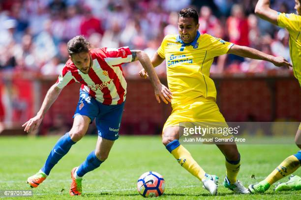 Angel Montoro of UD Las Palmas duels for the ball with Duje Cop of Real Sporting de Gijon during the La Liga match between Real Sporting de Gijon and...