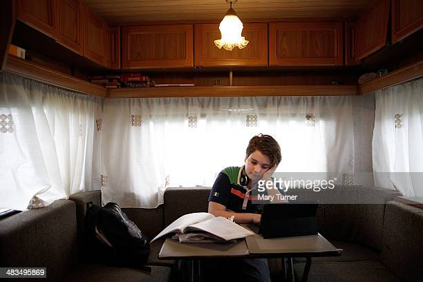 Angel Nicols aged 12 does his homework studies online before a show in the tiny caravan he shares with his mother as he travels around England with...