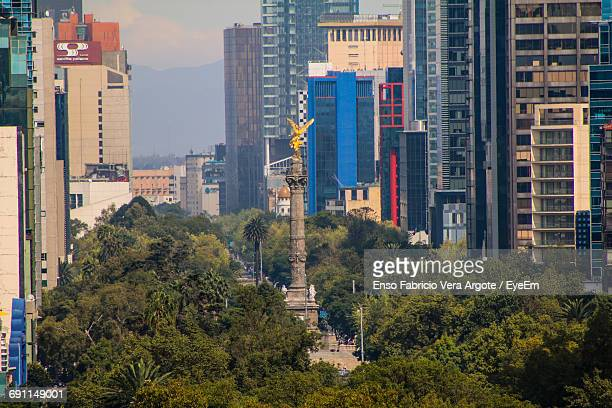 angel of independence against buildings in city - independence monument mexico city stock pictures, royalty-free photos & images