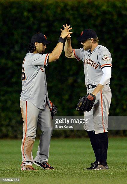 Angel Pagan and Hunter Pence of the San Francisco Giants celebrate their win over the Chicago Cubs at Wrigley Field on August 21, 2014 in Chicago,...