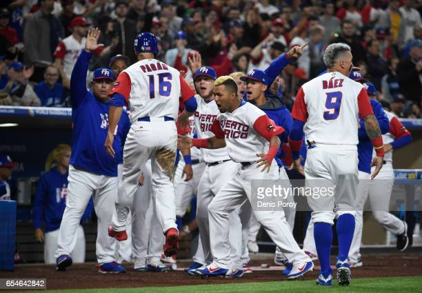 Angel Pagan of Puerto Rico is congratulated after scoring during the first inning of the World Baseball Classic Pool F Game Four between the United...