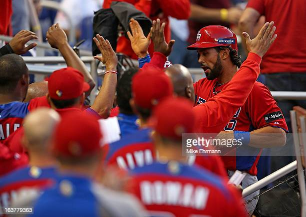 Angel Pagan of Puerto Rico is congratulated after scroing during a World Baseball Classic second round game against the United States at Marlins Park...