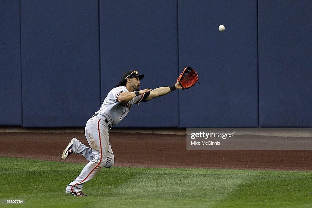 Angel Pagan #16 of the San Francisco Giants just misses this catch in centerfield allowing Aramis Ramirez of the Milwaukee Brewers a double during the sixth inning at Miller Park on August 07, 2014 in Milwaukee, Wisconsin.