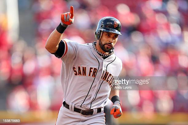 Angel Pagan of the San Francisco Giants rounds the bases after hitting a solo home run to lead off the game against the Cincinnati Reds in Game Four...