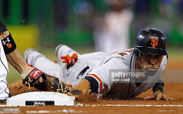 Angel Pagan of the San Francisco Giants slides safely back to first base before the tag of Logan Morrison of the Miami Marlins during a game at...
