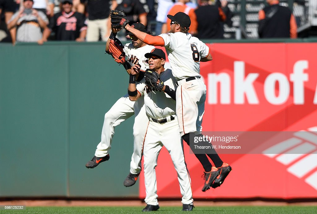 Angel Pagen #16, Gorkys Hernandez #66 and Hunter Pence #8 of the San Francisco Giants celebrate defeating the Arizona Diamondbacks 4-2 at AT&T Park on August 31, 2016 in San Francisco, California.