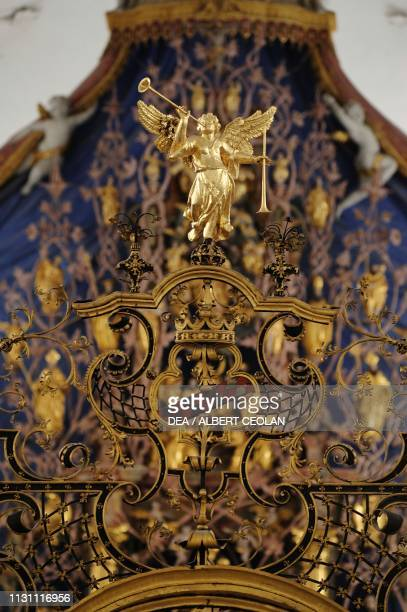 Angel playing the Trumpet of Judgment statue on the gate at the entrance to the high altar, church of the Cistercian Abbey of Stams, Tyrol, Austria,...