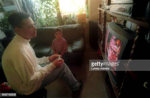 Angel plays video games with his nephew inside the Harlem projects in New York City in November 1999 Angel's mother is aware that her son dresses as...