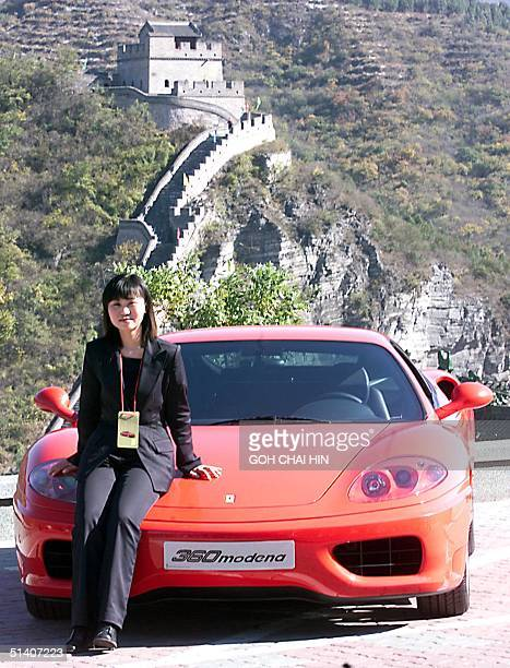 Angel Qu the first Chinese owner of the new Ferrari Modena 360 poses with her car against a backdrop at the Great Wall of China during a launch of...