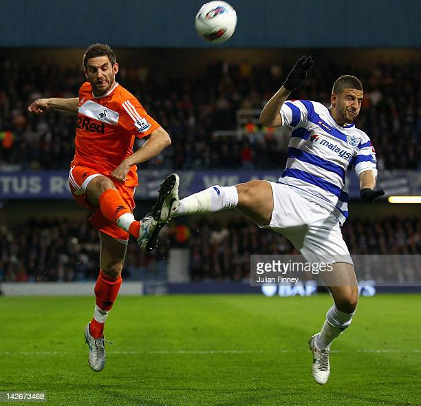 Angel Rangel of Swansea City and Adel Taarabt of Queens Park Rangers battle for the ball during the Barclays Premier League match between Queens Park...