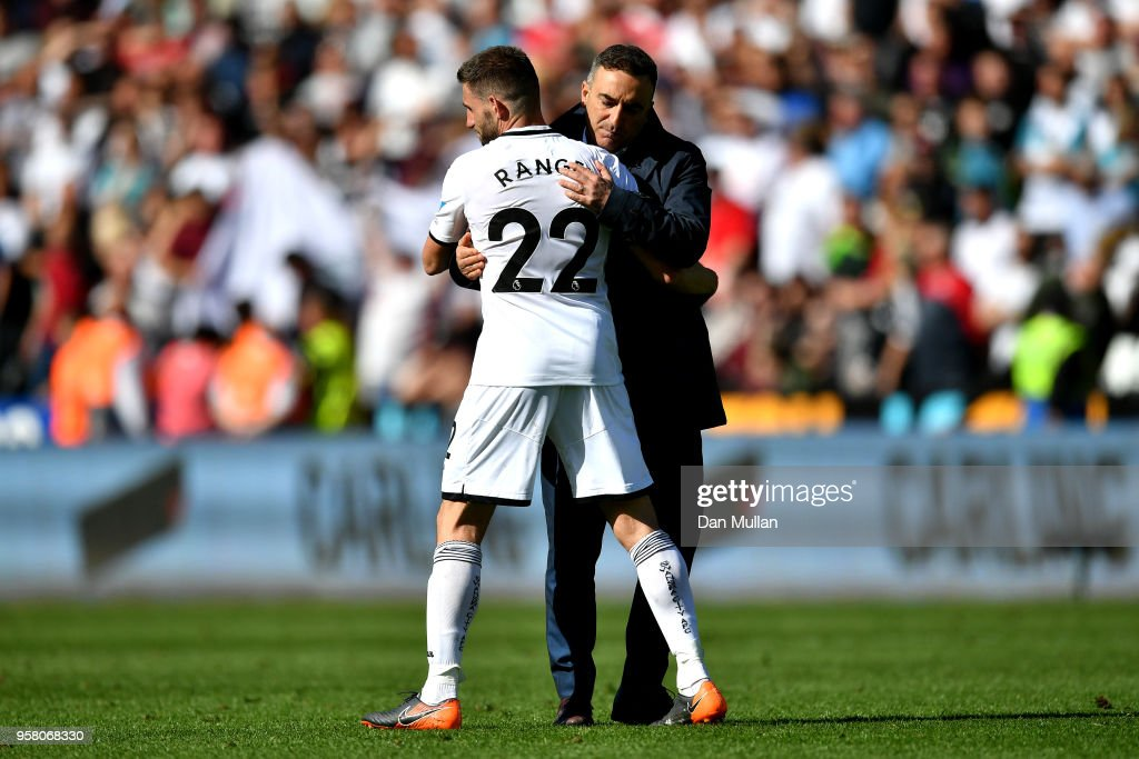 Angel Rangel of Swansea City and Carlos Carvalhal, Manager of Swansea City hug after the Premier League match between Swansea City and Stoke City at Liberty Stadium on May 13, 2018 in Swansea, Wales.