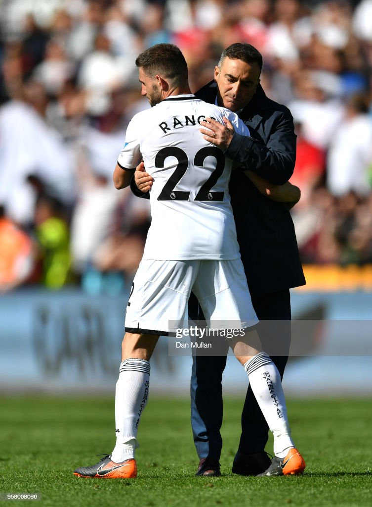Angel Rangel of Swansea City is embraced by Carlos Carvalhal, Manager of Swansea City after the Premier League match between Swansea City and Stoke City at Liberty Stadium on May 13, 2018 in Swansea, Wales.