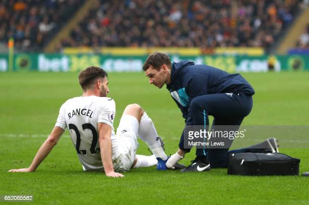 Angel Rangel of Swansea City receives treatment from the medical team during the Premier League match between Hull City and Swansea City at KCOM...