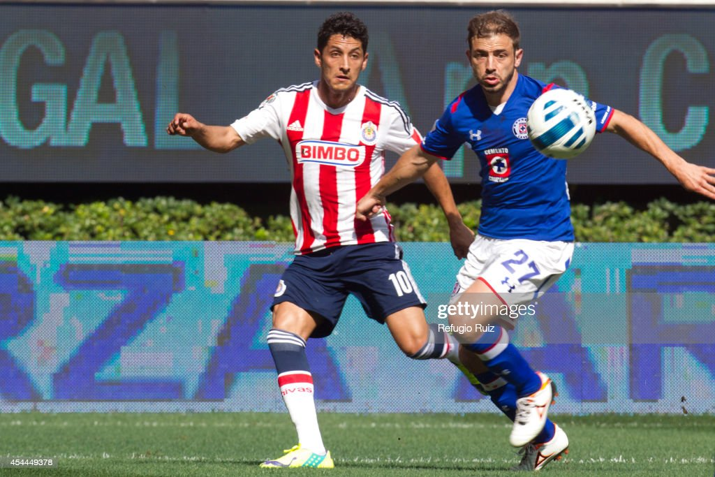 Angel Reyna of Chivas (L), fights for the ball with Hernan Bernardello of Cruz Azul (R) during a match between Chivas and Cruz Azul a as part of Apertura 2014 Liga MX at Omnilife Stadium on August 31, 2014 in Guadalajara, Mexico.