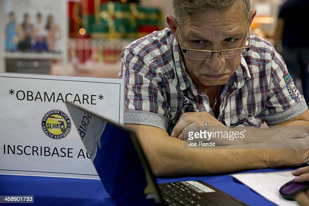 Angel Rivera looks at his health care options available with an insurance agent from Sunshine Life and Health Advisors as he tries to sign up for a...