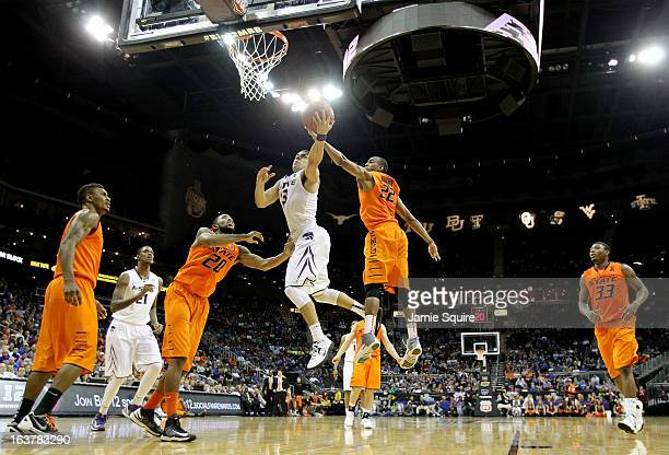 Angel Rodriguez of the Kansas State Wildcats shoots against Michael Cobbins and Markel Brown of the Oklahoma State Cowboys in the second half during...