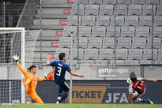 Angel Romero of Paraguay scores a disallowed goal past Kosuke Nakamura of Japan during the international friendly match between Japan and Paraguay at...