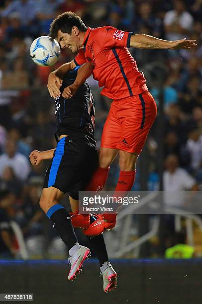 Angel Sepulveda of Queretaro jumps for the ball with Facundo Erpen of Morelia during a 8th round match between Queretaro and Morelia as part of the...
