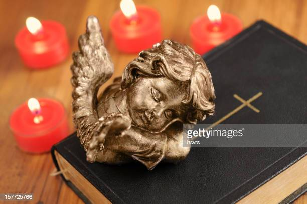 Angel sleeping on bible in front with Advent candles burning