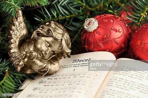 Angel sleeping on christian hymnal book with christmas ornaments