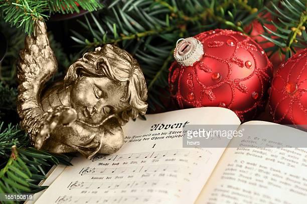 angelo che dorme sulla christian innario libro con ornamenti di natale - avvento foto e immagini stock