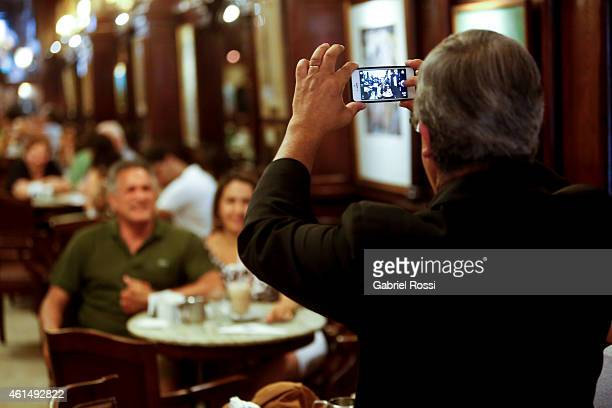 Angel Sosa waiter at Cafe Tortoni for 38 years takes a picture for two customers on December 19 2014 in Buenos Aires Argentina Cafe Tortoni was...