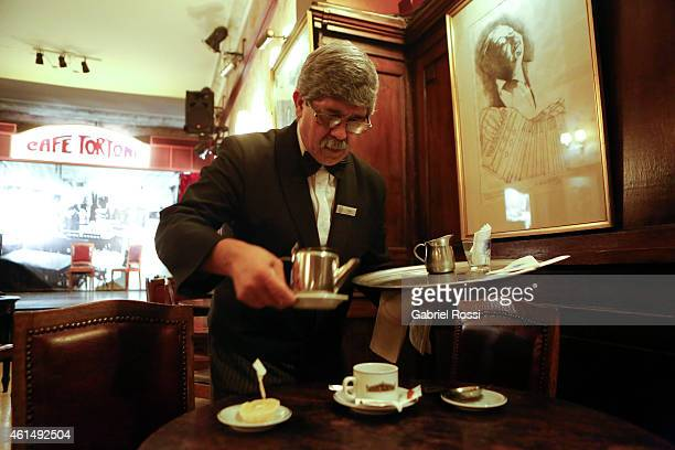 Angel Sosa waiter at Cafe Tortoni poses for pictures serving tea at the table Jorge Luis Borges used to sit at Cafe Tortoni on December 18 2014 in...