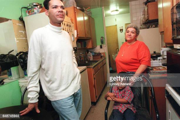 Angel stands next to his mother and nephew inside the Harlem projects in New York City in November 1999 Angel's mother is aware that her son dresses...