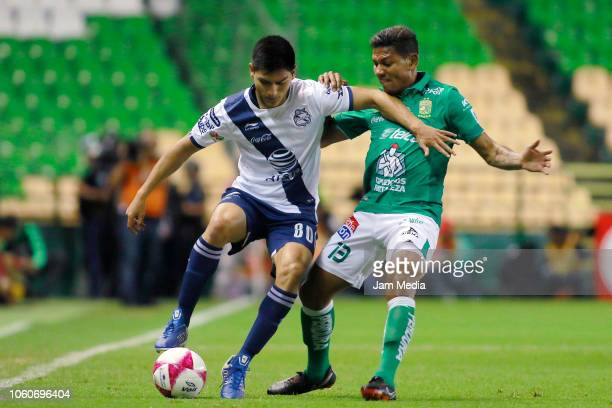 Angel Tecpanecatl of Puebla fights for the ball with Alexander Mejia of Leon during the 14th round match between Leon and Puebla as part of the...