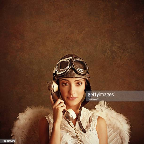 angel wearing pilot helmet and goggles talking on the phone