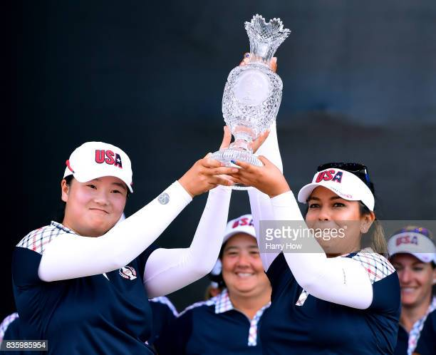 Angel Yin and Lizette Salas of Team USA hold up the Solheim Cup after defeating Team Europe 16 1/2 to 11 1/2 during the final day singles matches of...
