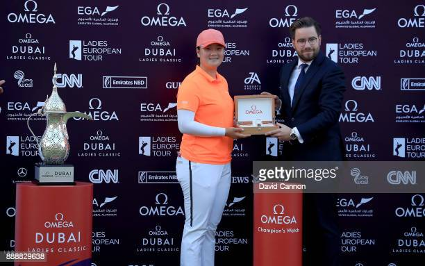 Angel Yin of the United States is presented with the champions watch by Henri Burrus the Area Sales Manager for Omega Watches after her playoff...