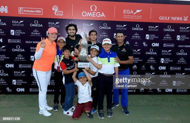 Angel Yin of the United States poses with the trophy and the Emirates Junior Golf Association Juniors after her playoff victory during the final...