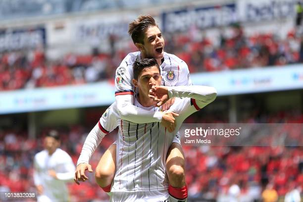 Angel Zaldivar of Chivas celebrates with teammate Isaac Brizuela after scoring his first goal during the third round match between Toluca and Chivas...
