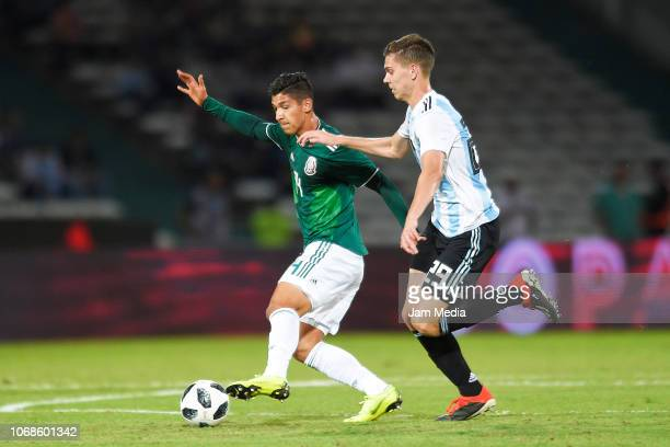 Angel Zaldivar of Mexico battles for possession with Juan Foyth of Argentina during a friendly match between Argentina and Mexico at Mario Kempes...