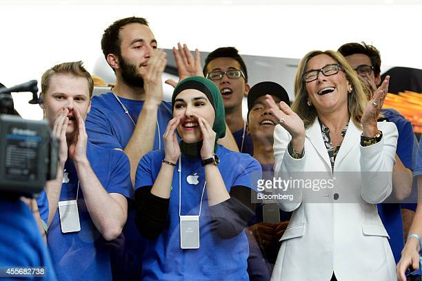 Angela Ahrendts, senior vice president of retail and online stores at Apple Inc., right, and employees cheer before opening the doors to the...