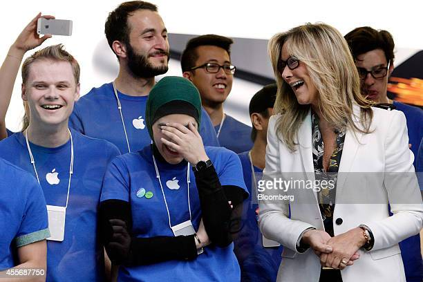 Angela Ahrendts, senior vice president of retail and online stores at Apple Inc., right, and employees react before opening the doors to the...