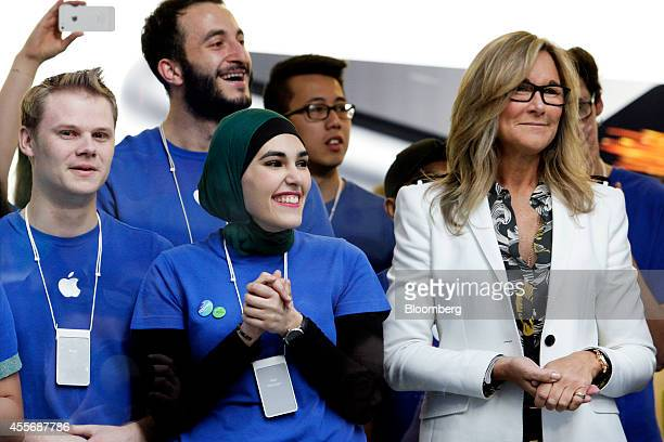 Angela Ahrendts, senior vice president of retail and online stores at Apple Inc., right, and employees look on before opening the doors to the...