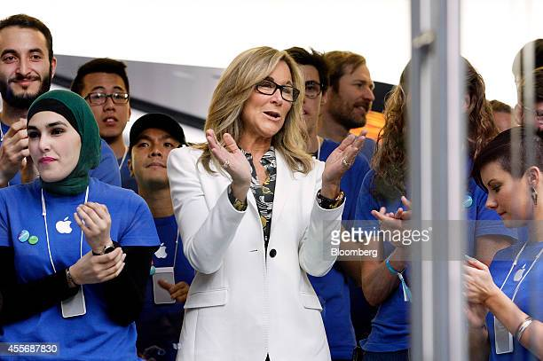 Angela Ahrendts, senior vice president of retail and online stores at Apple Inc., center, and employees cheer before opening the doors to the...