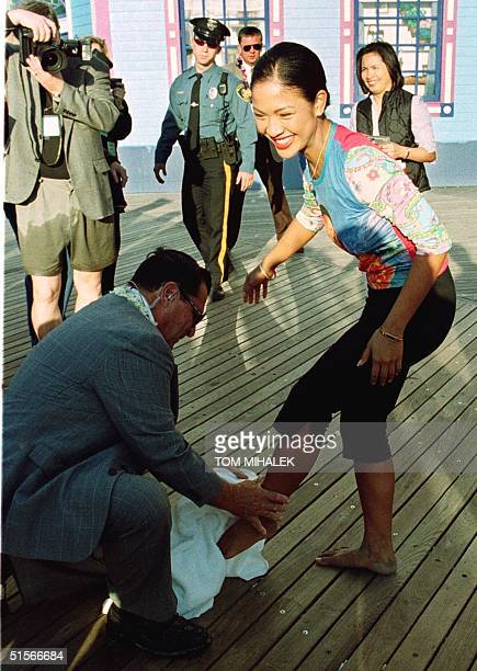 Angela Baraquio Miss America 2001 has her feet dried off by a pageant official after taking the traditional dip into the Atlantic Ocean on the first...