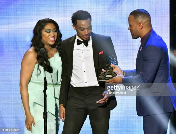 Angela Burgin and Devon Franklin present Jonathan McReynolds with the Artist of the Year award during the 34th annual Stellar Gospel Music Awards at...