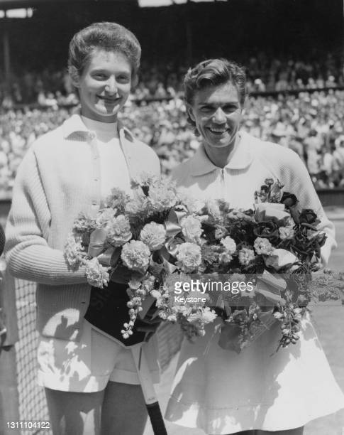 Angela Buxton of Great Britain and Shirley Fry of the United States pose for photographs on Centre Court carrying bouquets of flowers before their...