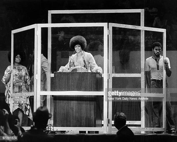 Angela Davis speaking at Madison Square Garden behind a foursided 7foot high bulletproof glass shield