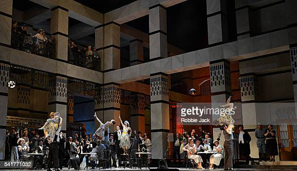 Angela Gheorghiu as Magda de Civry and Charles Castronovo as Ruggero Lastouc with artists of the company in the Royal Opera's production of Giacomo...