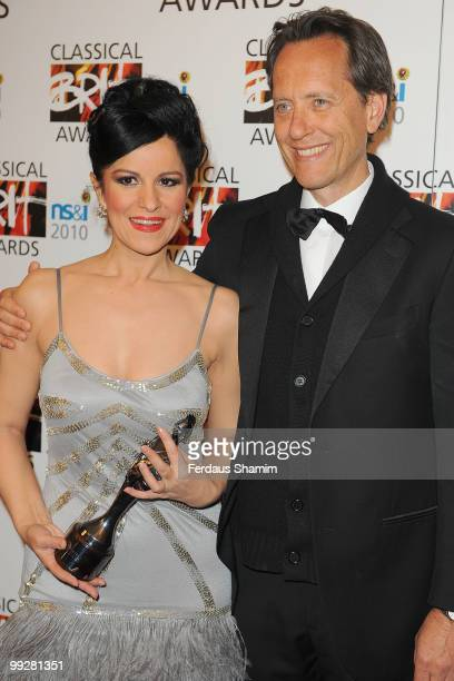Angela Gheorghiu poses with The Female Artist of the Year Award with with Richard E Grant in the Winners Room at the Classical BRIT Awards at Royal...