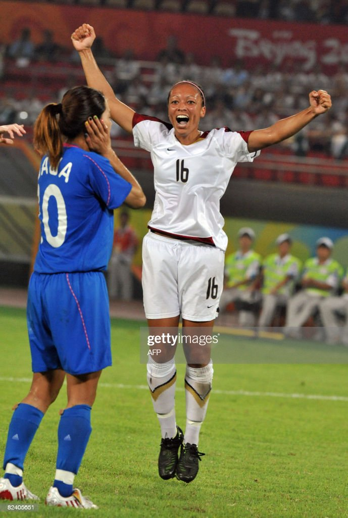 Angela Hucles of the US (R) jumps up to celebrate her goal next to Homare Sawa of Japan during their Beijing 2008 Olympic Games women's soccer semi-final match in Beijing on August 18, 2008. The US won 4-2.