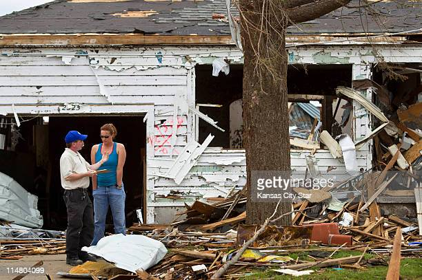 Angela Jennings, right, listens to Jeff Maxwell, left, her insurance agent, in Joplin, Missouri, on Thursday, May 26 following the tornado that swept...