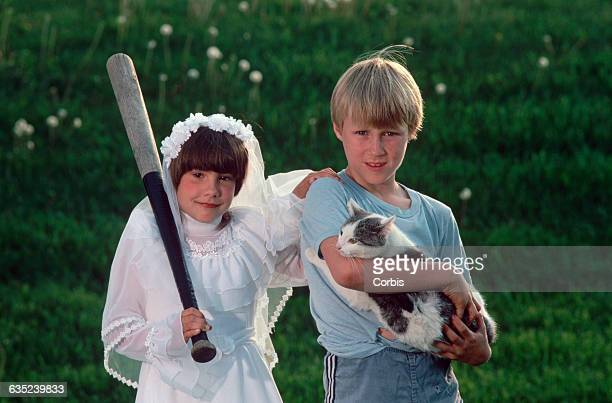 Angela Lowe in her first communion dress and holding a baseball bat stands with her brother Trevor who is holding their cat Dot